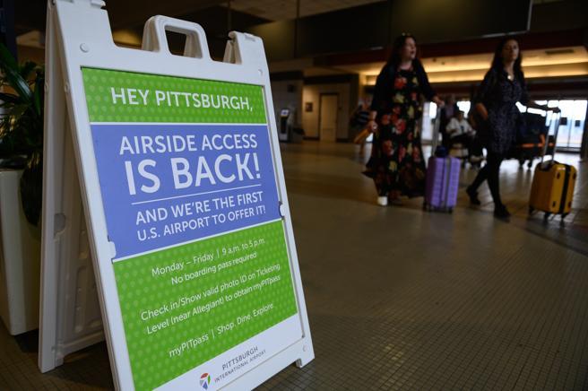 Los viajeros pasan un letrero con información sobre pases de acceso para no viajeros en el Aeropuerto Internacional de Pittsburgh (PIT) en Moon Township, Pennsylvania, EE. UU., (Justin Merriman / Bloomberg)